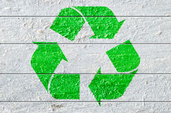 Green recycle symbol painted on a white natural textured wood. Stock Photo