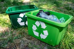 Green recycling boxes with plastic trash standing. On lawn royalty free stock image