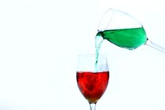 Green into Red. Green water pouring into Red Stem Glass Royalty Free Stock Image
