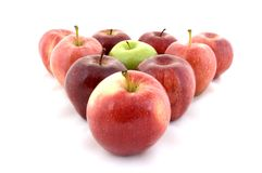 Green in Red. A green apple in a triangle of red apples Stock Photo