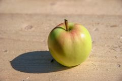 Green with red apple lies on a wooden bar on a sunny day. Selective focus. royalty free stock photo
