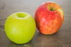 Green and red apple on the table Royalty Free Stock Photography