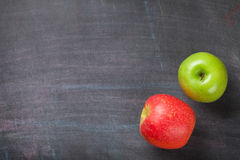 Green and red apples on blackboard or chalkboard background Royalty Free Stock Images