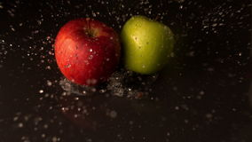 Green and red apples falling on wet black surface stock video