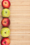 Green and red   apples lie on  bamboo mat Stock Photo