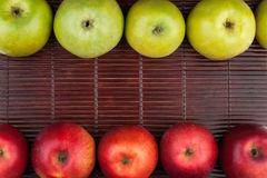 Green and red apples lie on the bamboo mat Stock Images