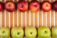 Green and red apples lie on the bamboo mat Royalty Free Stock Photo