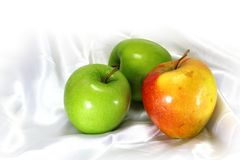 Green and red apples on a white satin background. Royalty Free Stock Photography