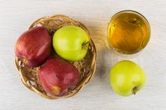 Green, red apples in wicker basket, glass of apple juice Stock Photo