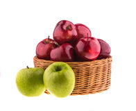Green and red apples in a wicker baskets Stock Photo