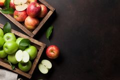 Green and red apples in wooden box stock images