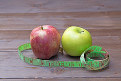Green and red apples wrapped with measuring tape Stock Image
