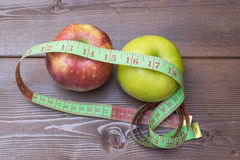 Green and red apples wrapped with measuring tape Royalty Free Stock Images