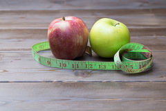 Green and red apples wrapped with measuring tape Stock Photo