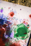 Green red blue blots white paper lying on a wooden surface Royalty Free Stock Images