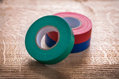 Green red blue rolls of insulating tape on wooden Royalty Free Stock Photography