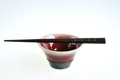 Green red ceramic bowl with wooden chopsticks Royalty Free Stock Photos