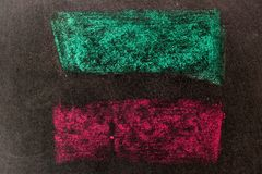 Green and red chalk drawing in line shape on black board. Background royalty free stock photos