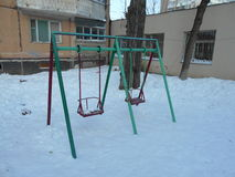 Green and red children's swing in the snow park area of ​​the city. On a winter day Royalty Free Stock Images