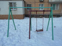 Green and red children's swing in the snow park area of ​​the city. On a winter day Royalty Free Stock Photo