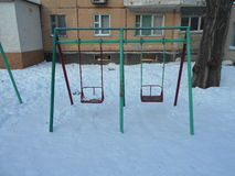 Green and red children's swing in the snow park area of ​​the city Stock Photography