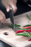 Green and red chilie peppers being cut on a wooden board Stock Images