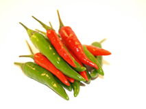 Green and Red Chillies. A pile of Green Finger Chillies and Bird Eye Chillies on a white background royalty free stock photo