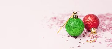 Green Red Christmas New Year balls holographic glitter confetti form of stars on pink background Flat Lay copy space. Holiday. Baubles, beautiful Decoration royalty free stock images