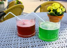 Green and red cocktail with straw in restaurant Stock Image
