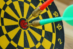 Green and red darts pin in the center of dartboard as business g. Oals or targets concept Royalty Free Stock Photos
