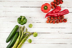 Green and red fresh seasonal vegetables on white wooden table Royalty Free Stock Photography