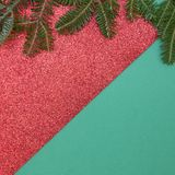 Green and gleaming red Christmas or New Year background with minimalistic design. Green and red gleaming Christmas or New Year background with a natural spruce Stock Images