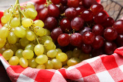 Green and red grape in basket on a grey wooden background Stock Image