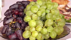Green and red grapes on a platter stock video