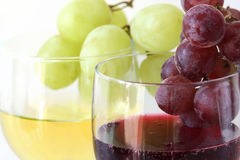 Green and red grapes on the white and red wine glasses. (main focus on red grapes Stock Photos