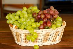 Green and red grapes in the wicker basket. Green and red grapes in a wicker basket Stock Photo