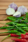 Green and red  hot chili peppers. Green and red hot chili peppers and garlic on a wooden table Stock Image
