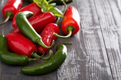Green and red hot pepper on table Royalty Free Stock Photos