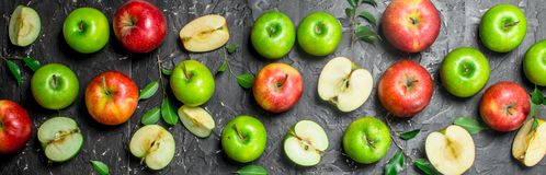 Green and red juicy apples with foliage and Apple slices. On black rustic background royalty free stock photos
