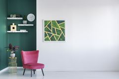 Green and red living room. Red chair against white and green wall with painting in living room interior with copy space Stock Photography