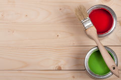 Green and red paint in the bank with brush on the light wooden background with copy space for your text. Top view Royalty Free Stock Image