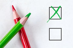 Green and red pencils with marking checkbox Stock Photography