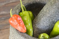 Green and red pepper in mortar Stock Photo