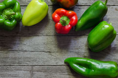Green and red pepper on wooden background Royalty Free Stock Photos