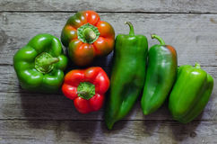Green and red pepper on wooden background Royalty Free Stock Photo
