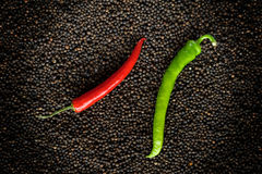 Green and red peppers on black peppercorns Stock Photography