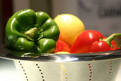 Green and red peppers in a bow. Green and red peppers bell in a stainless bowl Royalty Free Stock Image