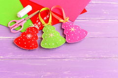 Green, red and pink Christmas trees crafts, scissors, white thread, needle, felt sheets set on a lilac wooden background Stock Photos