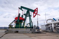 Green and red pumpjack, oil horse, oil derrick pumping oil well with dramatic cloudy sky background stock image