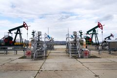 Green and red pumpjack, oil horse, oil derrick pumping oil well with dramatic cloudy sky background stock photos